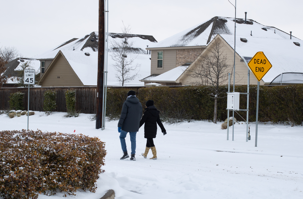 Mckinney, TX USA - February 17, 2021: Street view of Texan walking on the road after snowstorm — Stock Image