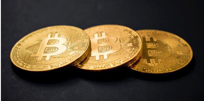 Three Bitcoin coins lying on a table