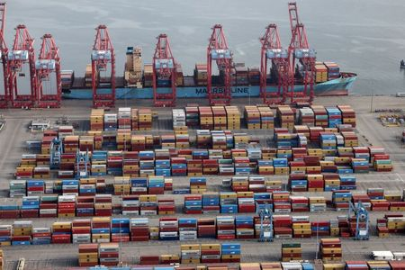 Shipping containers are unloaded from a ship at