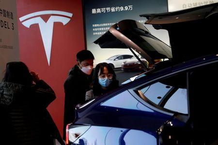 Visitors wearing face masks check a China-made Tesla