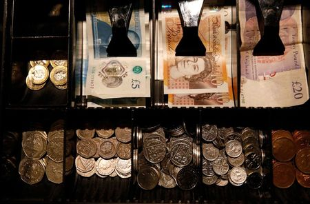 Pound Sterling notes and change are seen inside a cash resgister in a coffee shop in Manchester