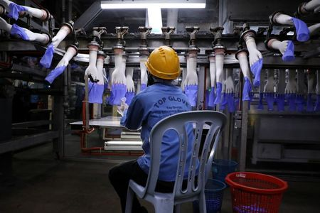 FILE PHOTO: A worker inspects newly-made gloves at Top Glove