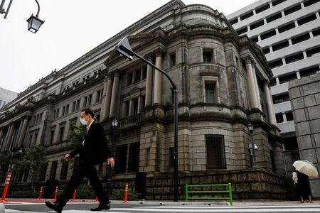 FILE PHOTO: A man wearing a protective mask walks past the headquarters of the Bank of Japan amid the coronavirus disease (COVID-19) outbreak in Tokyo