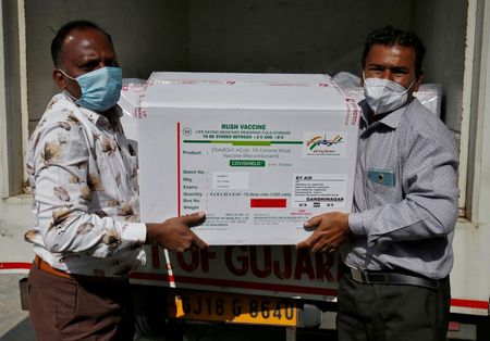 Officials unload boxes containing vials of COVISHIELD vaccine