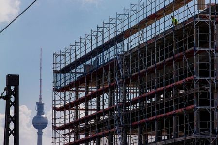 A worker is seen behind scaffoldings at a