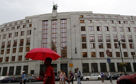 FILE PHOTO: A man holds an umbrella in front of the Czech National Bank in Prague