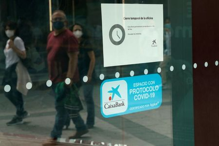 People walk past a closed Caixabank's branch during a one-day