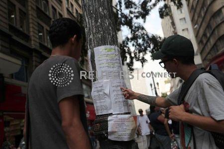 Homens observam anúncios de emprego em rua no centro de