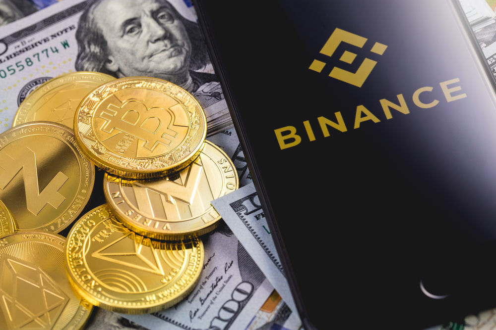 Apple iPhone and Binance logo, with dollars and cryptocurrency.